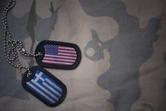 Armeefreier raum, Erkennungsmarke mit Flagge von Staaten von Amerika und Griechenland auf dem kakifarbigen Beschaffenheitshinterg Lizenzfreie Stockfotos