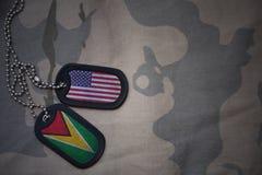 Armeefreier raum, Erkennungsmarke mit Flagge von Staaten von Amerika und Guyana auf dem kakifarbigen Beschaffenheitshintergrund Lizenzfreie Stockfotos