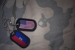 Armeefreier raum, Erkennungsmarke mit Flagge von Staaten von Amerika und Haiti auf dem kakifarbigen Beschaffenheitshintergrund Stockfotografie