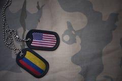 Armeefreier raum, Erkennungsmarke mit Flagge von Staaten von Amerika und Kolumbien auf dem kakifarbigen Beschaffenheitshintergrun Stockfotos