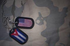 Armeefreier raum, Erkennungsmarke mit Flagge von Staaten von Amerika und Kuba auf dem kakifarbigen Beschaffenheitshintergrund Stockbild