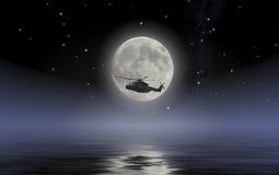 Armeehubschrauber, der auf Meer in einer Vollmondnacht kundschaftet Stockfoto