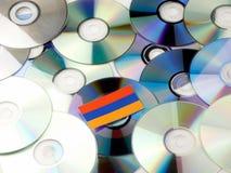 Armeense die vlag bovenop CD en DVD-stapel op wit wordt geïsoleerd Stock Afbeelding