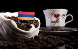 Armeense die vlag in een zak met koffiebonen op zwarte worden geïsoleerd Stock Foto's