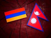 Armeense vlag met Nepali-vlag op een geïsoleerde boomstomp Stock Afbeelding