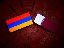 Armeense vlag met Qatari-vlag op een geïsoleerde boomstomp Stock Afbeeldingen