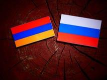 Armeense vlag met Russische vlag op een boomstomp Stock Foto's