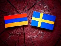 Armeense vlag met Zweedse vlag op een boomstomp Stock Foto