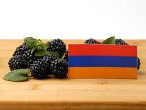 Armeense vlag op een houten die paneel met braambessen op a wordt geïsoleerd Stock Foto's