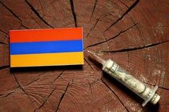 Armeense vlag op een stomp met spuit die geld inspuiten Royalty-vrije Stock Fotografie