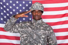 Armeesoldat, der vor amerikanischer Flagge begrüßt Stockfotos