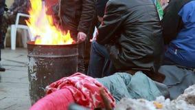 Armen die dichtbij het vat van het brandafval, de winter in openlucht verwarmen stock videobeelden
