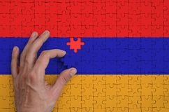 Armenia flag is depicted on a puzzle, which the man`s hand completes to fold.  royalty free illustration