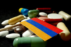 Armenian flag with lot of medical pills isolated on black background Royalty Free Stock Images