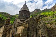 Armenian Geghard monastery. Geghard is a medieval monastery in the Kotayk province of Armenia, being partially carved out of the adjacent mountain, surrounded by Stock Photography