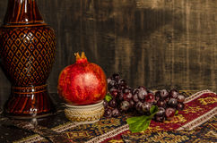 Armenian Still life on old fashion background. With wine pomegranate and grape Royalty Free Stock Image