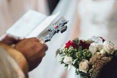 Armenischer Priester, der das Kreuz für Braut und Bräutigam hält stockbild