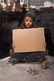 Armer Bettlerjunge auf der Straße mit einem Pappzeichen Lizenzfreies Stockfoto