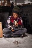 Armer Bettlerkinderjunge wiederholt das Geld, das er empfing lizenzfreie stockbilder