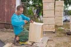 Armer ukrainischer Bauer, der Bienenstöcke macht Lizenzfreies Stockbild