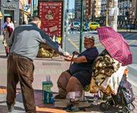 Armer ungesunder Mann, der um Almosen in der Straße von Murcia, Spanien bittet Mann gibt den Armen Geld stockbild