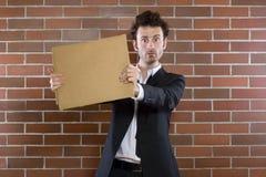 Armer unshaved Geschäftsmann plädiert mit einem unbelegten Zeichen Lizenzfreie Stockbilder