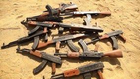 Armes à feu dans le sable de désert banque de vidéos