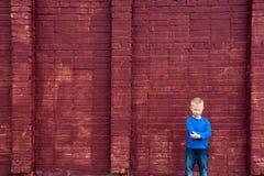 Armes kleines Kind nahe großer Wand Stockfotografie
