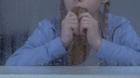Armes Mädchen, das Brot hinter regnerischem Fenster, unsichere Sozialschicht, Waisenhaus isst stock video