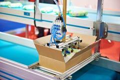 Armez le manipulateur de robot pour des produits d'emballage dans la boîte en carton photos stock