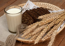 Armful of ears, fresh bread and a glass of milk on a straw tray with a linen napkin Stock Photography