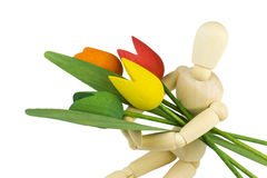 Armful of flowers. Amrful of flowers - a wooden symbol theme - mannequin dummy holding a bunch of colorful flowers - tulips Royalty Free Stock Photo