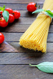 Armful of spaghetti, fresh tomatoes and basil Stock Photos
