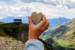 Armholding das Herz formte Stein vor der breiten Ansicht der schönen Landschaft des hohen Kaukasus in Kazbegi, Georgia Stockfoto
