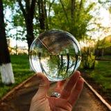 Armholding, welche die große transparente Glaskugel auf dem Finger auf dem Hintergrund im Freien umkippt Stockfotografie