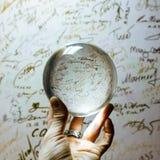 Armholding, welche die große transparente Glaskugel auf dem Finger auf dem Hintergrund im Freien umkippt Stockfoto
