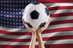 Armi che tengono palla con la bandiera dell'America Fotografia Stock