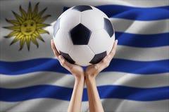 Armi che tengono palla con la bandiera dell'Uruguay Fotografia Stock