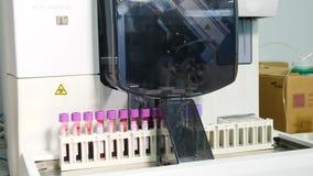 Armi del manipolatore robot con i contenitori o le provette con sangue sul trasportatore automatizzato a farmaceutico moderno archivi video