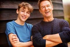 Armi dell'uomo Medio Evo felice del padre e del figlio adolescente piegate fotografie stock