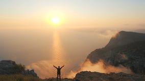 Armi della giovane donna di Silhuette stese osservando un bello tramonto drammatico sopra un mare da un'alta montagna in Crimea stock footage