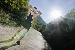 Armi di riscaldamento del corridore con il chiarore del sole Fotografia Stock