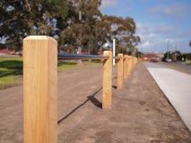 Armi in legno il palo della barriera ed il tubo della barriera fra una strada e un parco pubblico fotografia stock libera da diritti