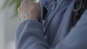 Armi rugose che riparano zaino alla parte posteriore Donna matura in maglia con cappuccio blu stock footage