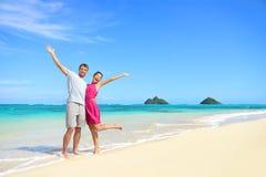 Armi spensierate felici delle coppie di vacanza della spiaggia alzate Immagine Stock Libera da Diritti