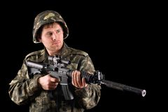Arming soldier and a rifle. In studio. Isolated Royalty Free Stock Images