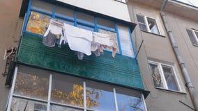 Armodlivbegrepp Linne torkas på balkongen på gatan lager videofilmer