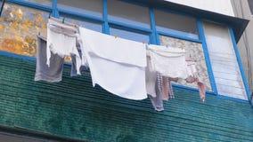 Armodlivbegrepp Linne torkas på balkongen på gatan stock video