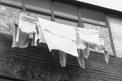 Armodlivbegrepp Linne torkas på balkongen på gatan Slapp fokus svart white fotografering för bildbyråer