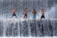 Armoedejongens die pret hebben bij de dam van Tukat Unda, Bali stock afbeelding